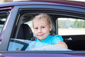 Happy Caucasians little blond child sitting inside of a car — Stock Photo