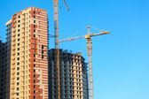 Construction of Highrise buildings with cranes. Blue sky background — Stock Photo