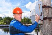 Caucasian senior worker man turning the power switch — Stock Photo
