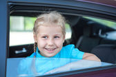 Happy Caucasians little girl looking out of a car window — Stock Photo