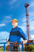 Senior Caucasian man in a working uniform with pipe valve. Looking fare away — Stock Photo