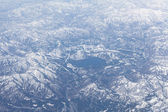 Mountain lake in the middle of snowcovered range, Japan. Aerial view — Stock Photo