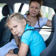 Unhappy girl sitting in child safety seat due mother fastening against the wishes — Stock Photo