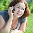 Stock Photo: Young woman with book speaking by phone on green grass