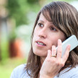 Caucasian young woman talking on the cell phone outdoor — Stock Photo