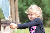 Girl washing hand in water dispenser outdoor — Stock Photo
