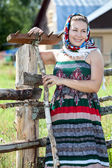 Country girl in sundress and headscarf against house — Stock Photo