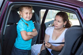 Caucasian girl does not want fastening in child safety seat in car — Stok fotoğraf