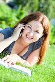 Giovane donna con libro parla al telefono — Foto Stock