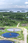Water treatment plant in evergreen woods and blue lakes — Stock Photo