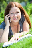 Young woman with book speaking by phone on green grass — Stock Photo