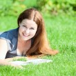 Smiling girl lying on green grass  — Stock Photo