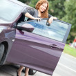 Woman standing behind a car — Stock Photo #31207413
