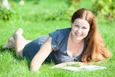 Woman lying on green grass — Stock Photo