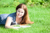 Smiling girl lying on green grass — ストック写真