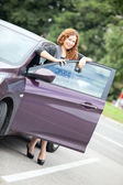 Woman standing behind a car — Stock Photo