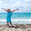 Little girl with hands up at sea beach — Stock Photo