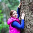 Smiling young woman touching stem of big pine in forest — Stock Photo