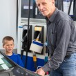Mature man with son refueling vehicle with gasoline — Foto Stock