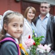 Little schoolgirl with her parents at the school — Stock Photo