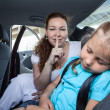 Mother with shh gesture when daughter asleep in car safety seat — Stock Photo