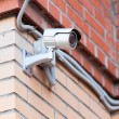 Video surveillance camera on brick wall — Stock Photo