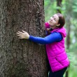 Joyful woman embracing pine stem — Stock fotografie