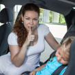Stock Photo: Mother showing shh gesture when daughter asleep in car safety seat