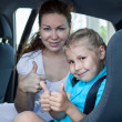 Stock Photo: Mother and child with thumb up gesture in car safety seat