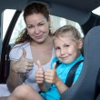 Stock Photo: Mother and child showing thumb up gesture in car safety seat