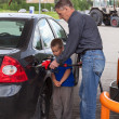 Stock Photo: Father with son refueling car on gas station together