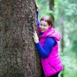 Stock Photo: Womhugging stem in forest