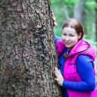 Attractive Caucasian woman walking and hugging a big pine tree trunk in the forest — Stock Photo