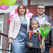 Stock Photo: Little schoolgirl with her parents at school