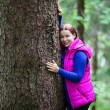 Stock Photo: Happy Caucasiwomembracing with huge tree in evergreen forest