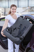 Young woman holding infant safety seat standing near car — Stock Photo