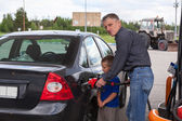 Young son looking at father refilling car at gas station — Stockfoto