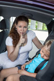 Mother showing shh gesture when daughter asleep in car safety seat — Stock Photo