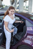 Woman holding buckle of infant safety seat installing it in the vehicle — Stock Photo