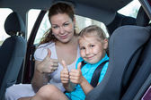 Mother and child showing thumb up gesture in car safety seat — Stock Photo