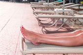 Female legs on sunbed at the pool — Stock Photo