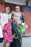 Little schoolgirl with her parents at the school — Stockfoto