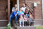 Big Caucasian family sitting in front of the house — Foto de Stock