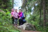 Mother with two small twins daughters in forest — Stock Photo