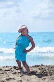 Little girl practicing yoga at sea beach in blue dress — Stock Photo