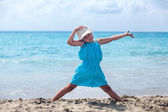 Little girl practicing yoga at sea beach — Stock Photo