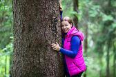 Mujer caucásica feliz abrazando con el enorme árbol en el bosque siempreverde — Foto de Stock