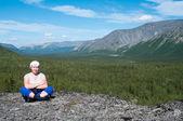 Woman sitting on mountain top — Stock Photo