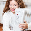 Stock Photo: Womembracing white oil heater