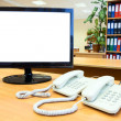 Monitor with telephones on desk in office — Stock Photo
